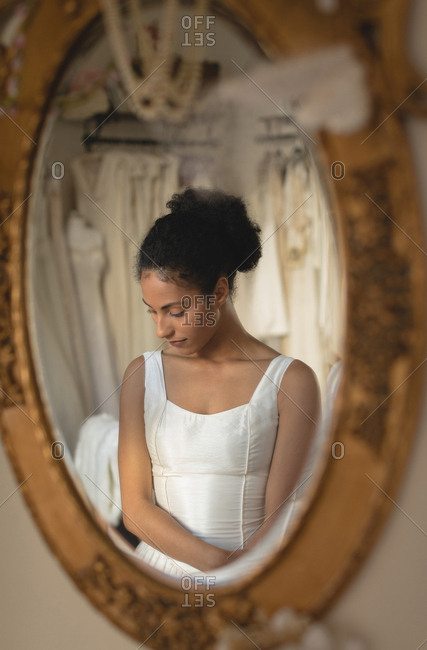 Reflection of young bride in a wedding dress in the mirror at boutique