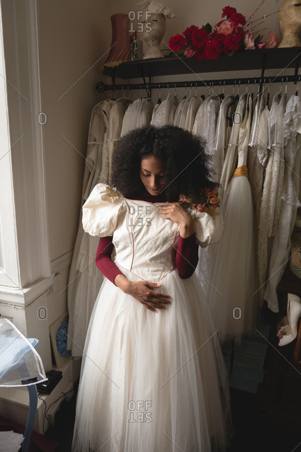 Young bride trying wedding dress from clothes hanger in the boutique