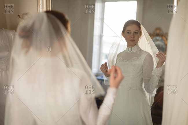 Young bride in a wedding dress looking at mirror in the boutique