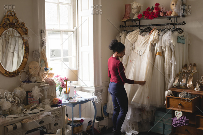 Young woman selecting wedding dress from clothes hanger at boutique