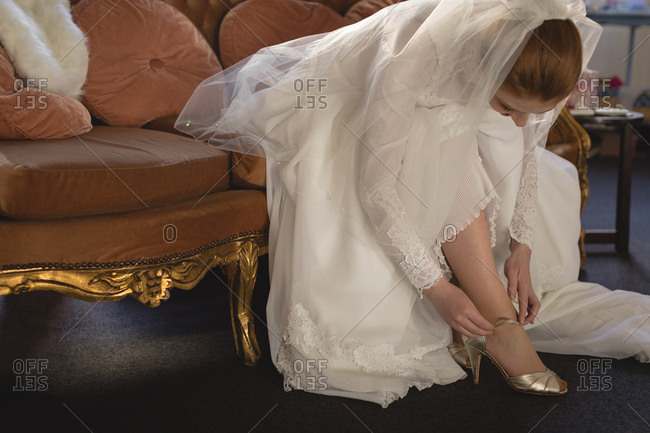 Young bride in wedding dress wearing high heels at boutique