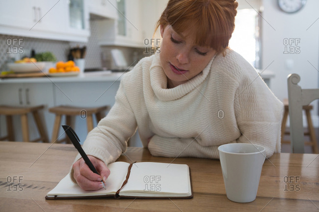 Young woman writing on a diary at home