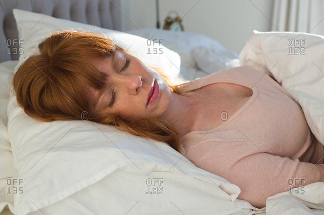 Woman sleeping in bedroom at home