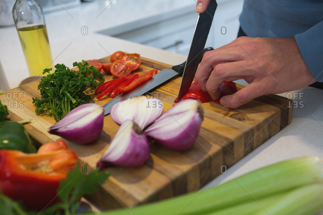 Mid section of man cutting vegetables in kitchen at home