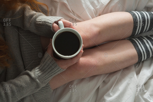 Woman holding mug of black coffee in bedroom at home