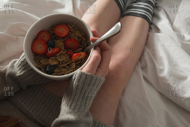Woman holding bowl of breakfast in bedroom at home
