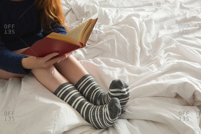 Woman reading a book in bedroom at home