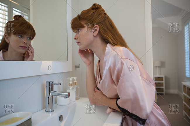 Woman looking at mirror in bathroom at home