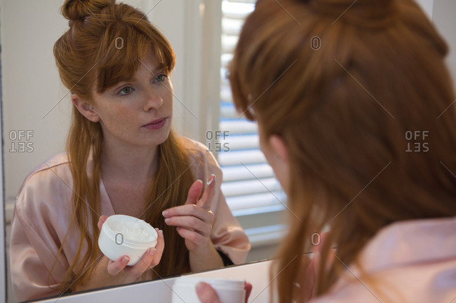 Woman applying cream on her face in bathroom at home