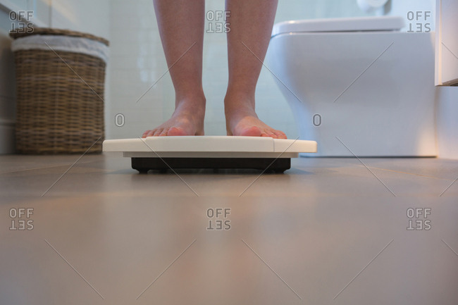 Low section of woman checking her weight on weighing scales at home