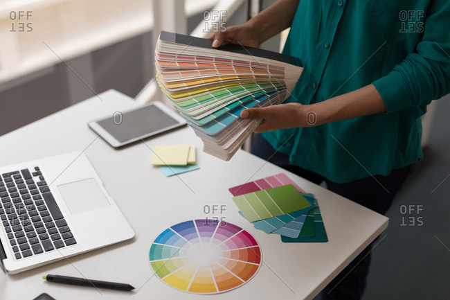 Female graphic designer holding color shade cards in office