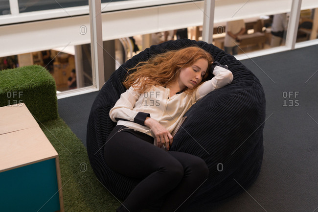 Female executive relaxing on bean bag in office