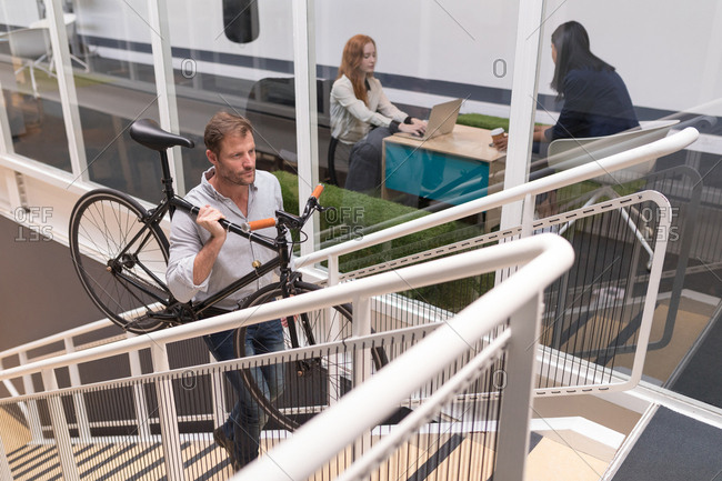 Male executive carrying cycle while moving upstairs in office