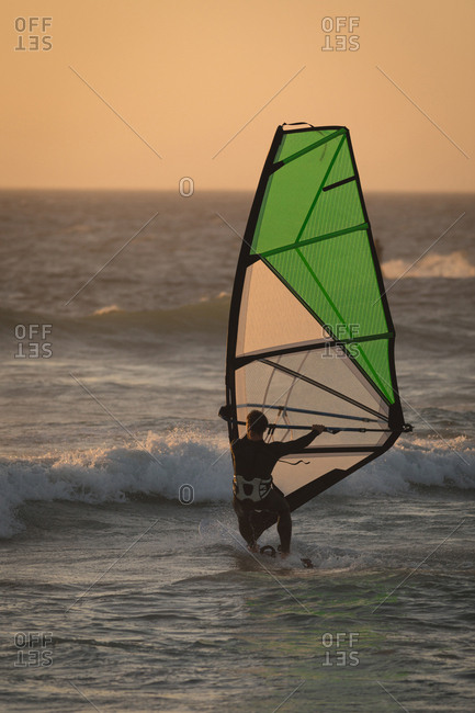 Male surfer surfing with surfboard and kite at beach