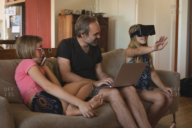 Father and daughters using electronic devices in living room at home