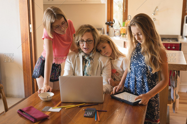 Mother and daughters using laptop and digital tablet at home