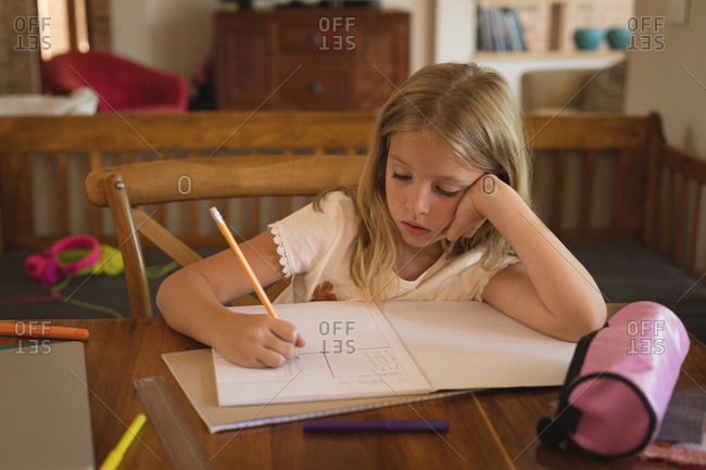 Adorable girl doing her homework at home