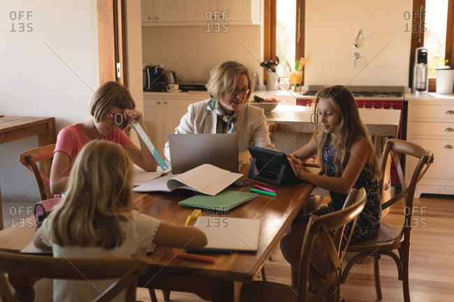 Mother using laptop while children dosing their homework at home