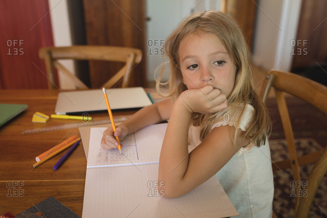 Thoughtful girl doing her homework at home