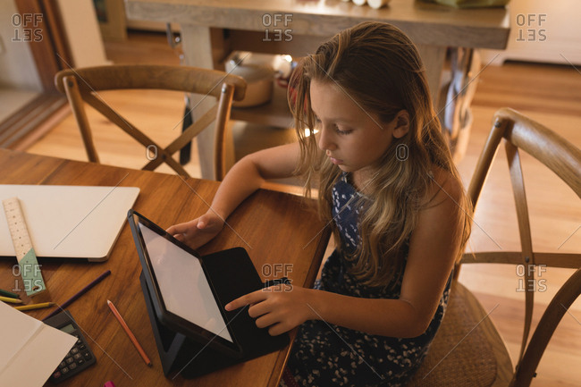 Attentive girl using digital tablet at home