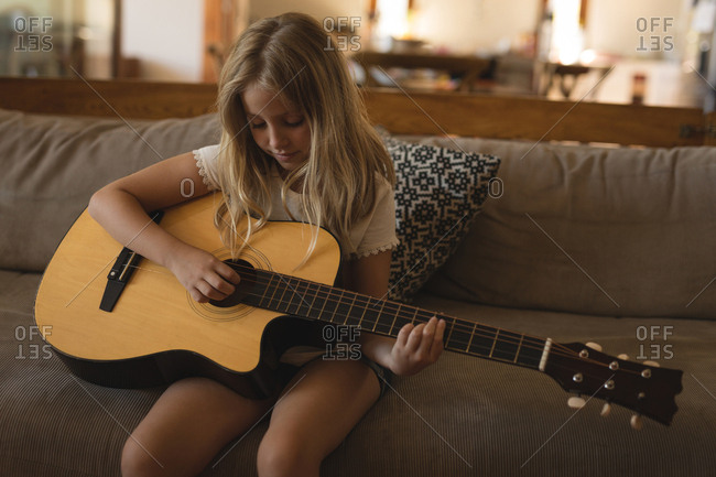 Girl playing guitar in living room at home
