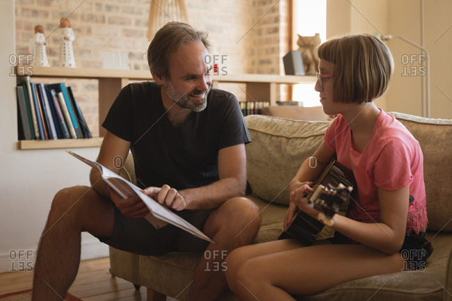 Father helping her daughter to play guitar in living room