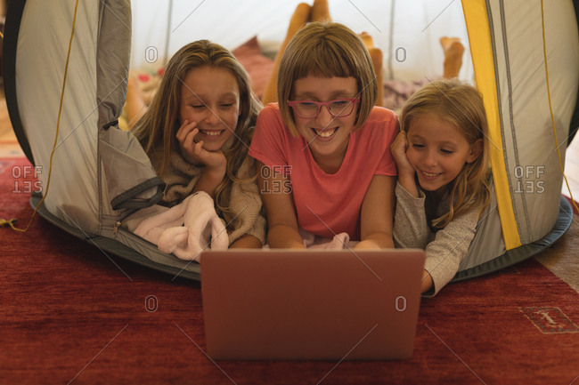 Happy siblings using laptop in a tent at home