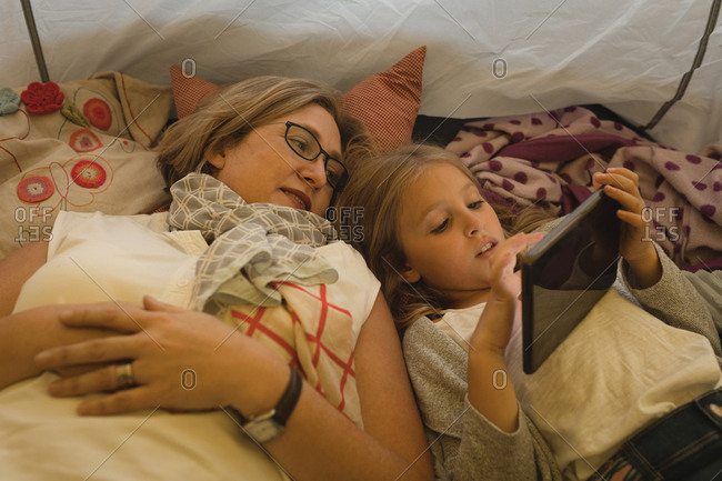 Mother and daughter using digital tablet in tent at home