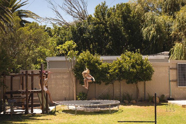 Girl jumping on trampoline in the garden on a sunny day
