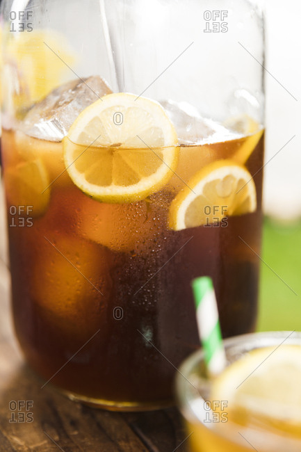 Pitcher full of iced tea with lemons