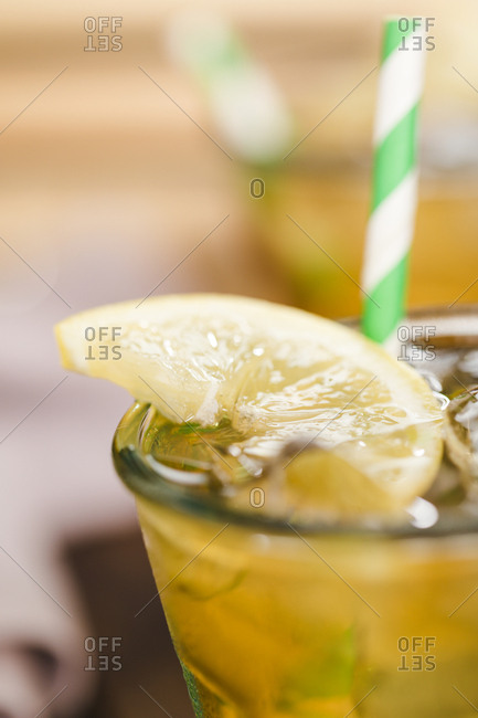 Close-up of drinking glass with lemonade iced tea and lemon wedge