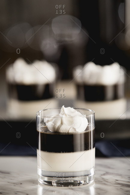 Black and white layered dessert topped with whipped cream