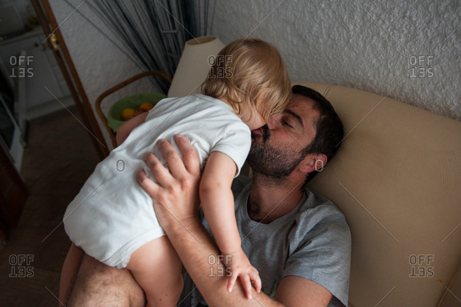 Father giving little daughter kisses