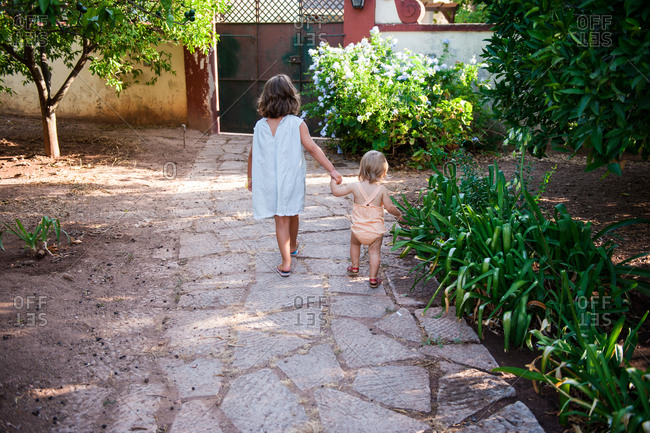 Little girl leading her younger sister down the garden path