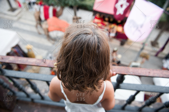 Rear view of little girl looking down at street parade