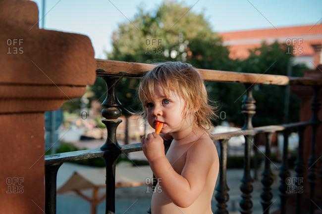 Little girl having snack on balcony on summer evening