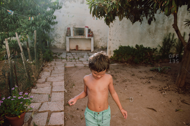 Young boy playing in backyard on summer evening