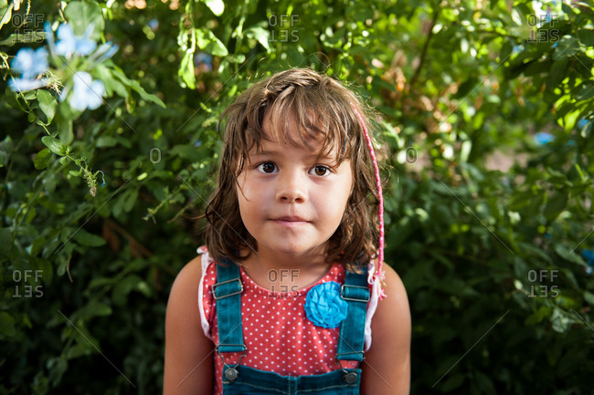 Portrait of young girl in backyard wearing polka dot top and dungarees
