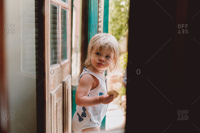 Little girl walking out of door snacking on cookie