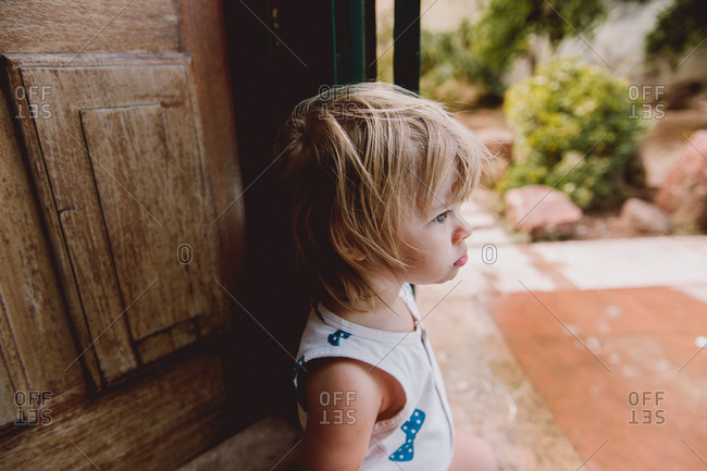Little girl standing at door deciding whether to go out or not