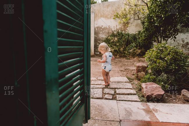Little girl taking tentative steps on garden path