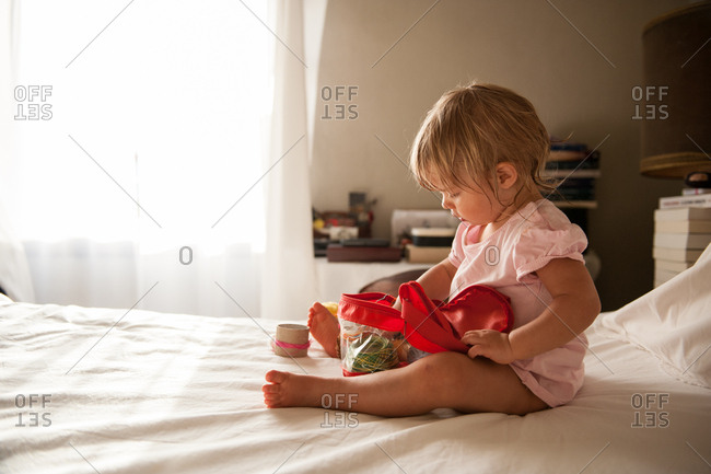 Little girl sitting on parent's bed concentrating on toys