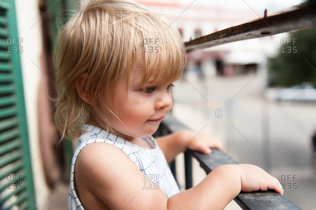 Little girl looking down at street from balcony