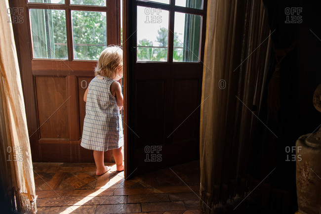 Little girl peeking out balcony door to see what is going on outside