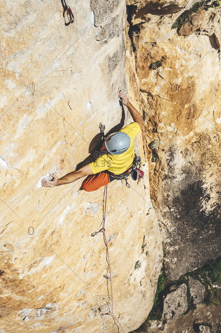 High angle view of Rock climber reaching across for a hold while rock climbing
