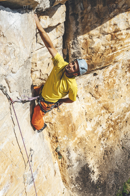 High angle view of Rock climber reaching back to chalk hands while climbing