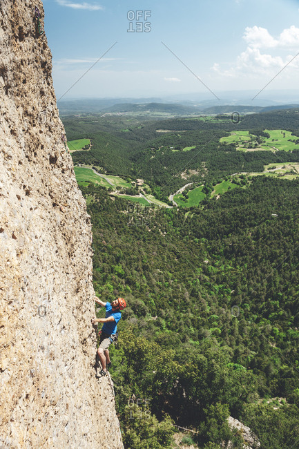 Berga, Spain - May 17, 2009: Wide angle view of climber contemplating next move on rock face with landscape in the background