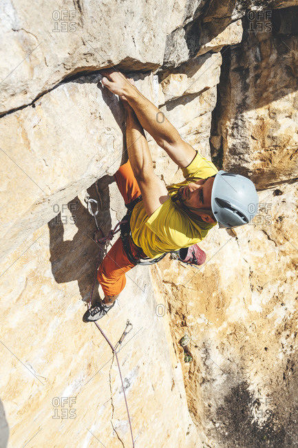 High angle view of Rock climber reaching over for next handhold on rock face