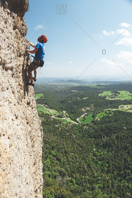 Berga, Spain - May 17, 2009: Wide angle view of climber on rock face with landscape in the background