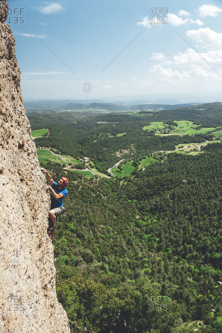 Berga, Spain - May 17, 2009: Wide angle view of rock climber reaching up for hold with landscape in the background
